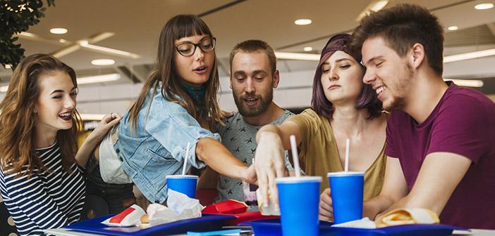 Un grupo de gente joven comiendo en un restaurante