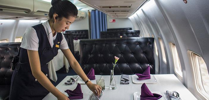 """Una camarera ultima los detalles del """"set up"""" de las mesas antes de comenzar un turno de comidas."""