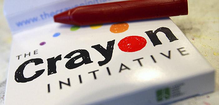 Lápiz de cera rojo encima de una caja pequeña con el logotipo de Crayon Initiative